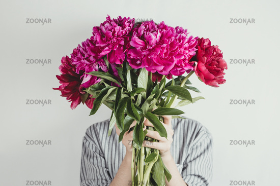 Faceless portrait of woman holding bouquet of violet and purple flowers, selective focus