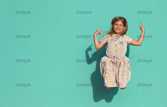 Happy girl jumping on green background