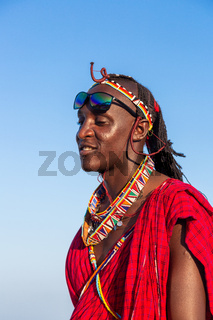 portrait of a smiling masai in traditional clothing, side view