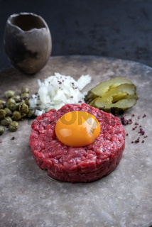 Gourmet tartar raw from beef fillet with yellow of the egg and gherkin with capers and onion as closeup on a modern design plate