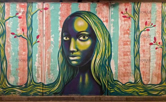 Young woman with long hairs, graffiti, underground passway Baratashvili Bridge, Tbilisi, Georgia