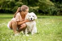 Frau mit Golden Retriever Hund im Garten