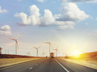 Wind turbines along highway at sunset