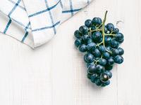 Dark grape bunch on white wooden table