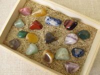 Tumbled gemstones in a wooden box with sand