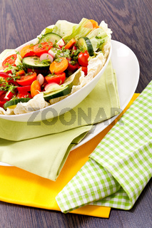 fresh mixed colorful salad on wooden table