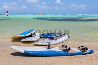 Windsurf boards lying on beach by  sea