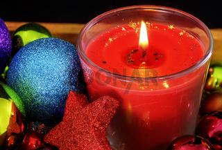 Eine brennde weihnachtliche Kerze im Glas und bunter glitzernder Weihnachtsschmuck