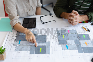 Midsection of diverse male and female colleague looking at blueprints and discussing
