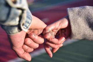 Close up photo of couple holding hands.