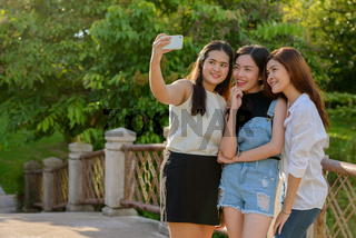 Three young Asian women as friends taking selfie together at the park