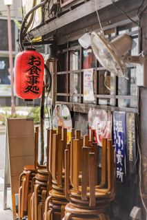 Old vintage retro japanese metal signs and red rice paper lantern where it is written 'Oshokujidokoro' which means 'Meal' on underpass Yurakucho Concourse wall under the railway line of the station Yurakucho. Japanese noodle stalls and sake bars revive th
