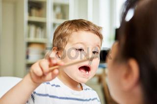 Kind untersucht spielerisch Kinderärztin mit Spatel