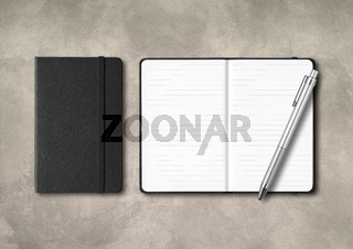Black closed and open lined notebooks with a pen on concrete background