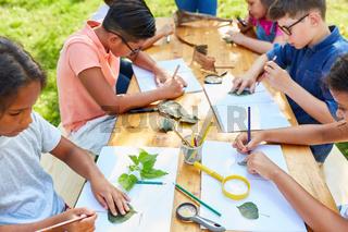 Kinder zeichnen und basteln zusammen im Ferienlager