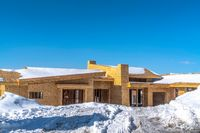 Home under construction amidst snowy terrain in Park City Utah viewed in winter