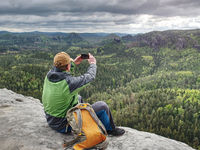 Ginger man takes photos with smart phone on rocky peak.