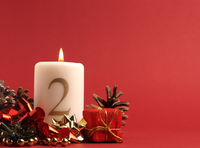 White candle with the number two burns, Advent background