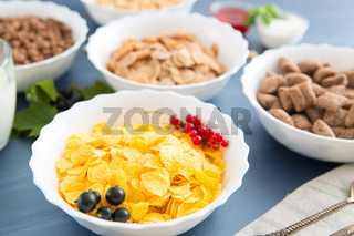 oatmeal with nuts and dried fruits on old white painted wooden table. Perfect breakfast Breakfast cereal mix: cornflakes, pads, muesli, multigrain flakes and chocolate balls