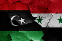 flags of Libya and Syria painted on cracked wall