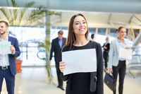 Frau mit Willkommen Schild am Flughafen