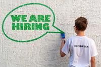 A boy in front of a white wall drawing a speech bubble with text WE ARE HIRING