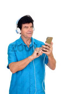 Portrait of mature handsome man using phone while listening to music