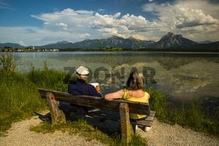 Älteres Ehepaar, Rentner, Parkbank, Hopfensee, bei Füssen, dahinter die Ammergauer Alpen, Ostallgäu, Allgäu, Bayern, Deutschland, Europa