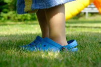 A young child is wearing too big shoes