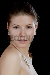 The girl in  necklace with naked shoulders on a black background