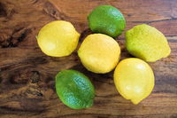 lemons and limes on a wooden table