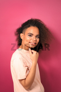 Charming passionate young African American girl with Afro hair looking positively at camera with one arm folded wearing peachy t-shirt isolated on pink background. Beauty concept