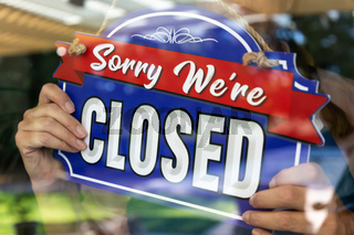 Female Store Owner Turning Sign to Closed in Window