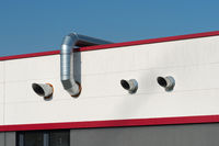 Stainless steel air ducts on a red roof
