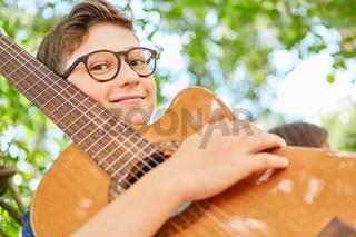 Lächelnder Junge als Musik Talent mit Gitarre