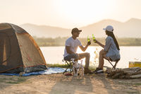 Young adult Asian couple drinking beer beside their tent with dog