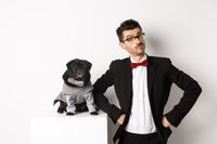Animals, party and celebration concept. Handsome young man and puppy in formal suits looking at camera, standing over white background
