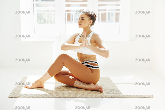 Нщгтп female in sportswear sitting with crossed legs and on mat