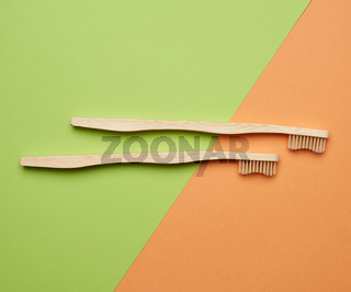 two wooden toothbrushes on a green orange background, plastic rejection concept