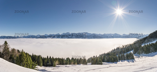 Fantastic panoramic view of snow mountains with blue Sky and Sun. Great panorama to Mountain Range above inversion valley fog layer. Ofterschwanger Horn, Alps, Allgau, Bavaria, Germany.