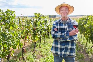 Zufriedener Weinbauer mit einem Glas Rotwein