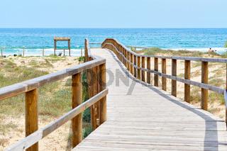 Wooden empty board walk leading through sandy dunes to Mediterranean Sea and beach of Los Arenales del Sol or Arenals del Sol. Costa Blanca, Europe, Spain. Espana