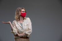 Blond young female in red protective mask against viruses, holds her head.