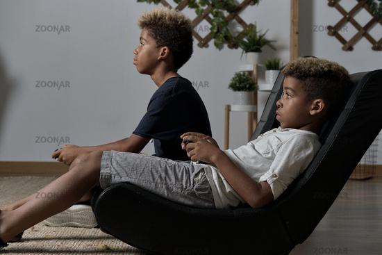 Two mixed race brothers play to play station seated together indoor. Alpha generation offspring addicted with virtual games problem concept