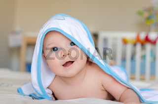 Smiling baby in a hooded towel after bath