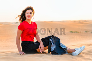 A beautiful girl with a backpack rests in the fantastic scenery of the red desert of Dubai