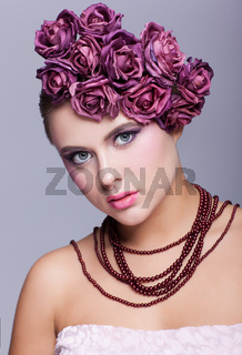 Beautiful young woman with artificial rouses on head necklace and dress on gray background