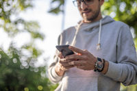 Smart looking man texting message on smartphone in park, back light
