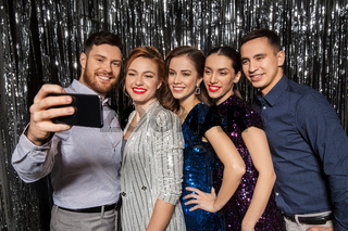 happy friends taking selfie by smartphone at party