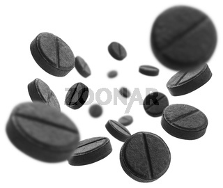 Black activated carbon tablets levitate on a white background